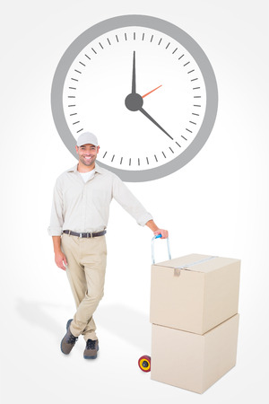 against the clock: Confident delivery man with cardboard boxes against clock Stock Photo
