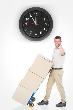 against the clock: Delivery man with cardboard boxes gesturing thumbs up against clock
