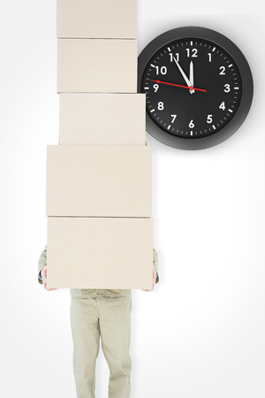 against the clock: Delivery man carrying stacked boxes against clock Stock Photo
