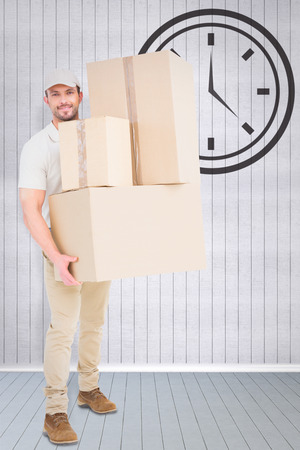 delivery room: Delivery man carrying cardboard boxes against grey room Stock Photo