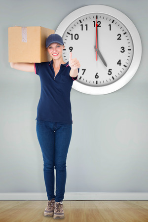 delivery room: Happy delivery woman holding cardboard box against room with wooden floor