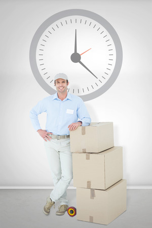delivery room: Confident delivery man leaning on stacked cardboard boxes against grey room Stock Photo