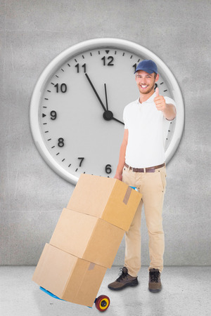 delivery room: Happy delivery man pushing trolley of boxes against grey room Stock Photo