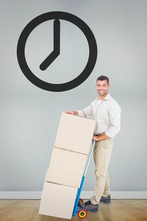sala parto: Felice l'uomo consegna con carrello di scatole contro stanza con pavimento in legno Archivio Fotografico