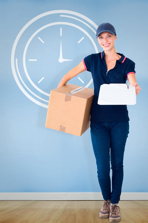 delivery room: Happy delivery woman holding cardboard box and clipboard against blue room with wooden floor