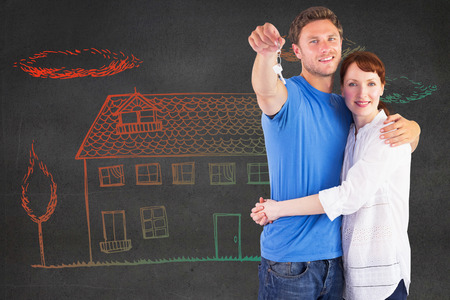 Couple holding keys to home against black wall photo