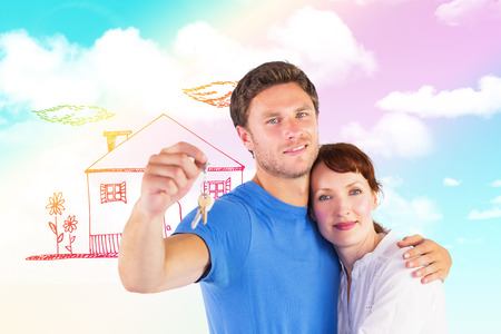 Couple holding keys to home against blue sky photo