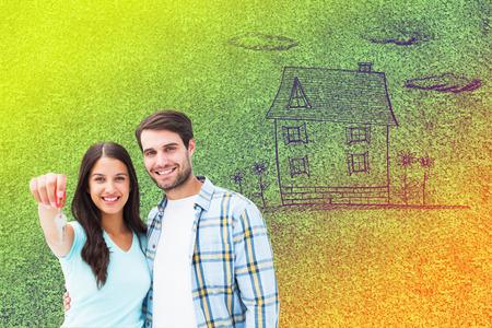 アストロ芝生面に対して幸せな若いカップル表示の新しい家の鍵 写真素材