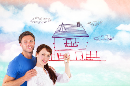 Couple holding keys to home against painted sky photo