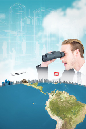 Surprised businessman looking through binoculars  against blue sky photo