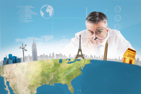 Mature businessman examining with magnifying glass against blue sky photo