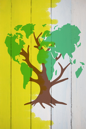 yellow earth: Earth tree against yellow paint on fence Stock Photo