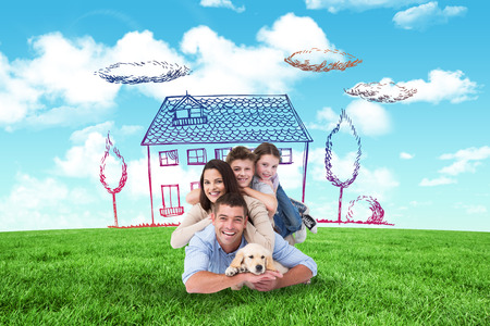 family on grass: Happy family lying on top of each other with dog against blue sky over green field