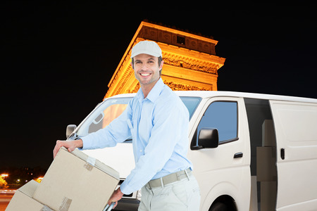 triumphe: Confident delivery man pushing trolley of cardboard boxes against arc de triumphe in france