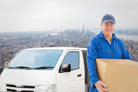 boiler suit: Happy delivery man holding cardboard box against new york