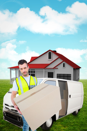 Delivery man holding cardboard box against blue sky photo