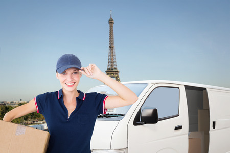 Happy delivery woman holding cardboard box  against eiffel tower photo