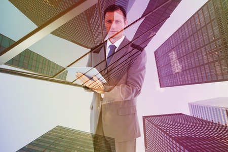 charismatic: Serious charismatic businessman holding a tablet computer against skyscraper