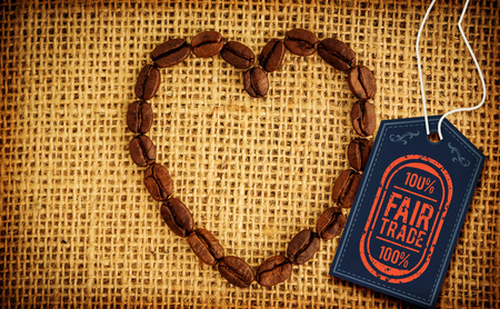 Fair Trade graphic against heart made out of coffee beans Stock Photo