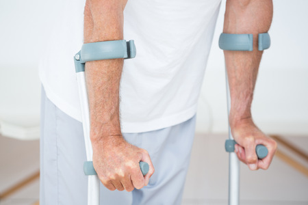crutch: Patient standing with crutch in medical office Stock Photo