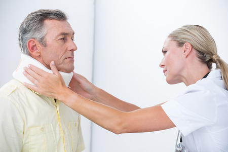 neck brace: Doctor examining patient wearing neck brace in medical office