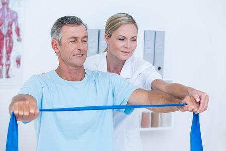 Arts onderzoekende haar patiënt terug in medisch kantoor Stockfoto
