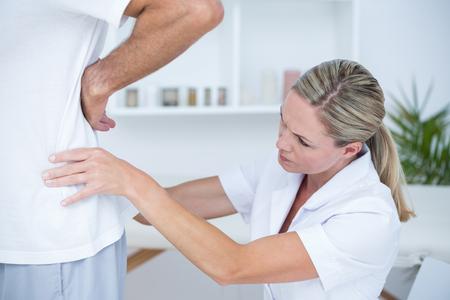 postural integration: Doctor examining her patient back in medical office