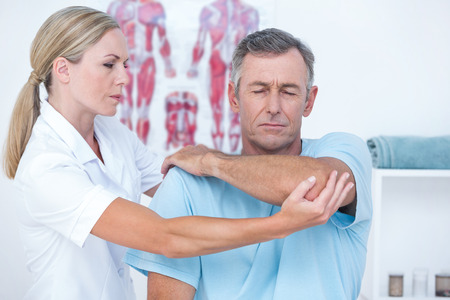 strength therapy: Doctor stretching a man arm in medical office Stock Photo