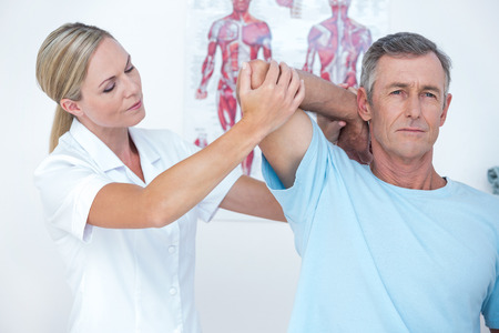relaxation massage: Doctor stretching a man arm in medical office Stock Photo