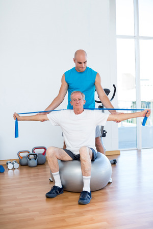 muscle retraining: Trainer examining his patient back in fitness studio Stock Photo