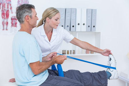 muscle retraining: Doctor examining her patient back legs in medical office