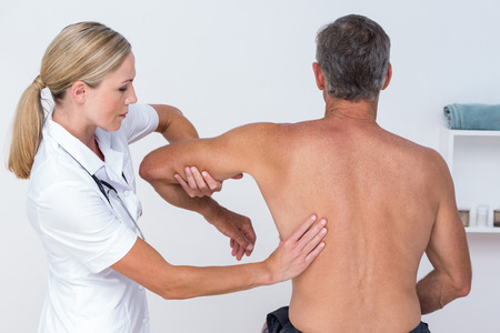 neuromuscular reeducation: Doctor examining her patient arm in medical office Stock Photo