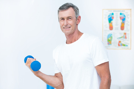 strength training: Patient looking at camera and lifting dumbbell in medical office Stock Photo