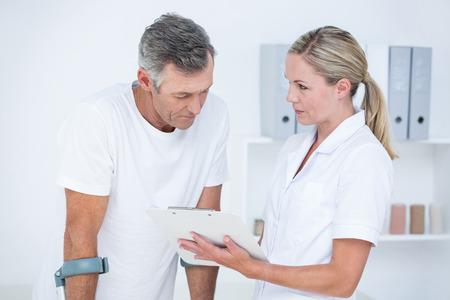 Arts toont klembord aan haar patiënt met kruk in medisch kantoor Stockfoto