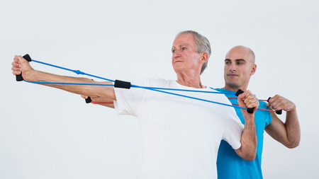 retraining: Old man stretching elastic in fitness studio