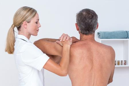 Doctor examining her patient shoulder in medical office