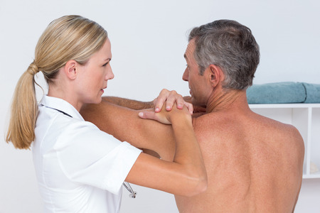 neuromuscular reeducation: Doctor examining her patient shoulder in medical office