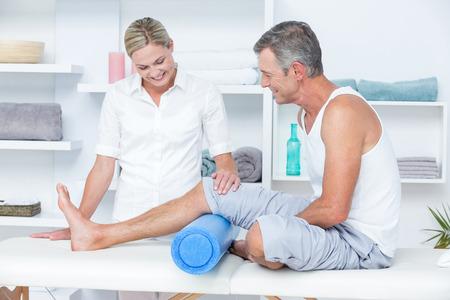医療事務に彼女の患者の足を調べる医師