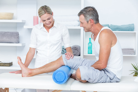 patient in bed: Doctor examining her patient leg in medical office Stock Photo