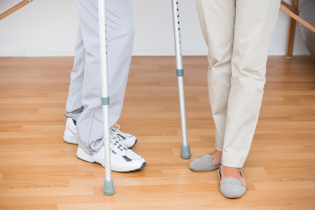 orthopedist: Doctor helping her patient walking with crutch in medical office