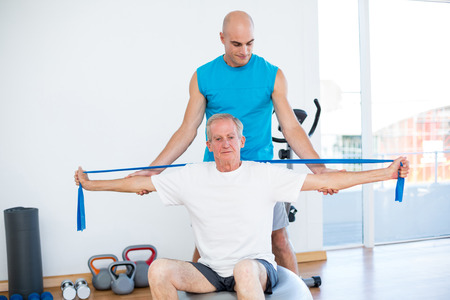 posture correction: Trainer examining his patient back in fitness studio Stock Photo