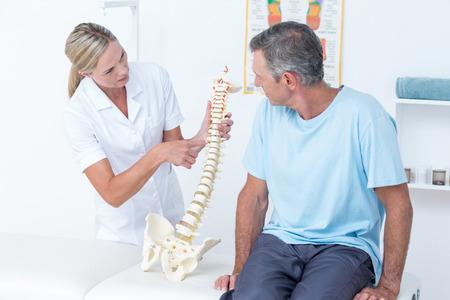 Arts die haar patiënt een ruggengraat model in medische kantoor