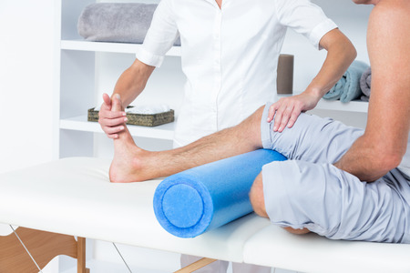 physiotherapy: Doctor examining her patient leg in medical office Stock Photo