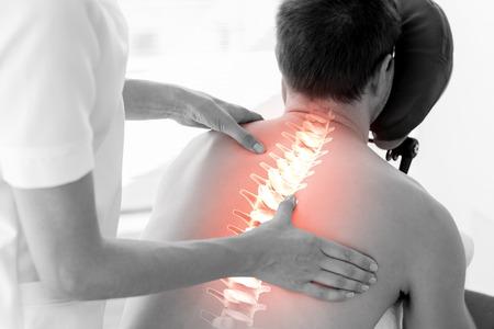 massage homme: Composite numérique de la colonne vertébrale en surbrillance de l'homme à la physiothérapie