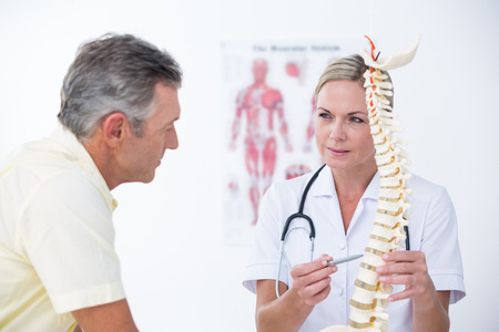 columna vertebral: Doctor que muestra su paciente un modelo de la columna vertebral en el consultorio médico