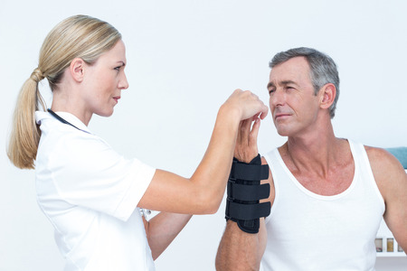 physical impairment: Doctor examining a man wrist in medical office Stock Photo