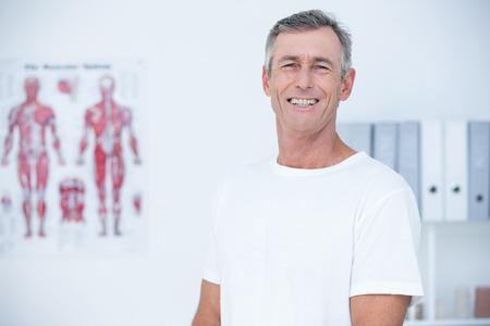 paciente: Paciente sonriente mirando a la cámara en el consultorio médico