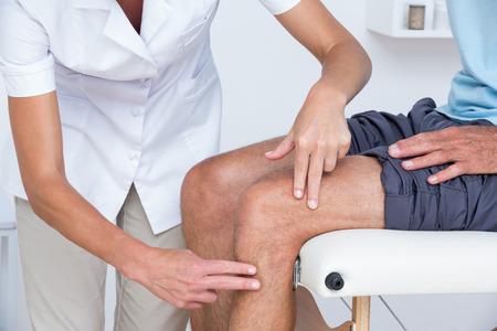 dolor muscular: Doctor que examina a su paciente de rodilla en el consultorio médico