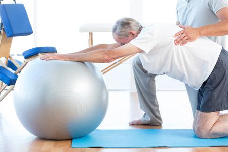 men exercising: Fisioterapeuta hombre que ayuda con la bola de ejercicio en la oficina médica