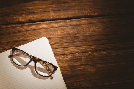 gafas de lectura: Libreta vac�a con gafas de lectura en un escritorio